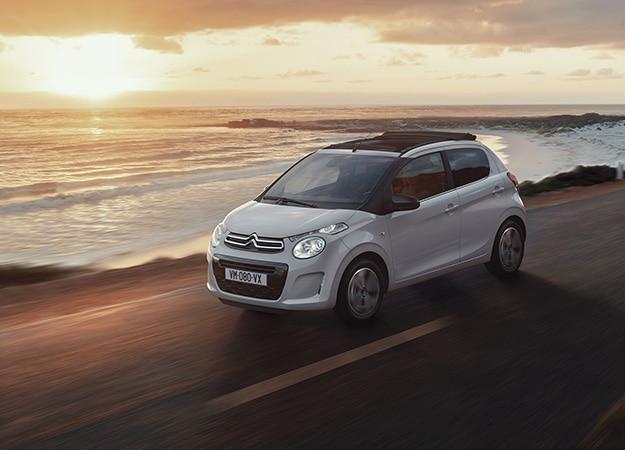 Citroën C1 sur une route en bord de mer, soleil levant
